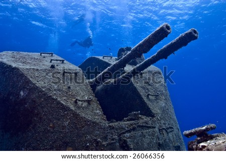 """A diver hovers over the deck gun of the sunken Russian frigate, The """"Tibbets"""".  Cayman Brac. - stock photo"""