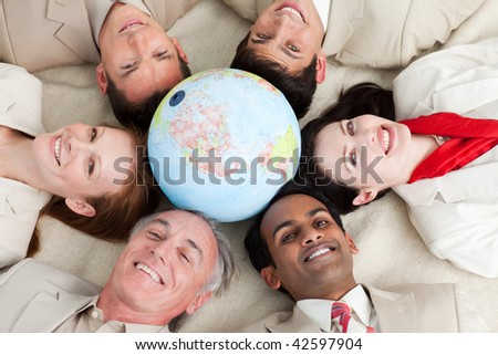 A diverse business people lying on the floor around a globe - stock photo