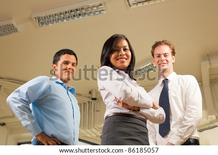 A diverse business team stands and looks confidently at the camera which is at a low angle - stock photo