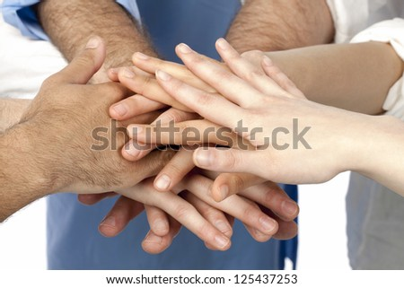 A diverse group of businesspersons with their hands together in form of teamwork and unity - stock photo