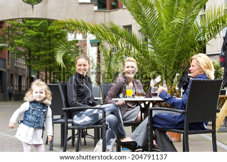 A diverse group of women, enjoying some leisure time around a table at a terrace, with the daughter (out of focus) playing cheerfully. Candid shot with copy space on top of the image. - stock photo
