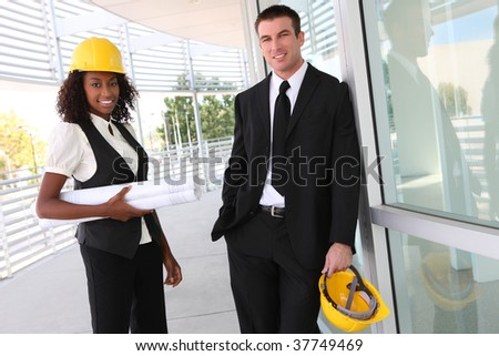 A diverse man and woman working as architect on a construction site - stock photo