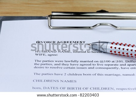 A Divorce contract on a lawyers desk along with a ball point pen for you to agree to. - stock photo