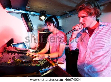 A DJ and a mc in action at a party in a nightclub. - stock photo