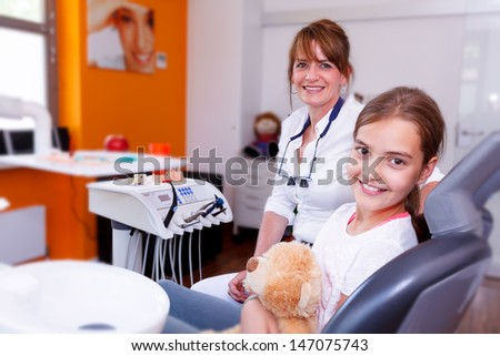 A doctor and teenager girl in a dentist surgery smiling in the camera. A doctor and a young girl smiling and looking the camera. - stock photo