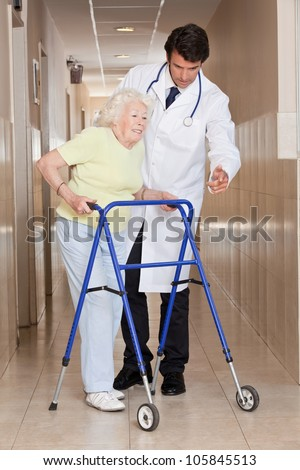 A doctor assisting a senior woman onto her walker. - stock photo