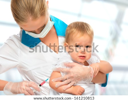 A doctor does injection child vaccination baby - stock photo