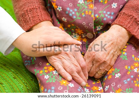 A doctor holding/ shaking an old woman's hand - part of a series. - stock photo
