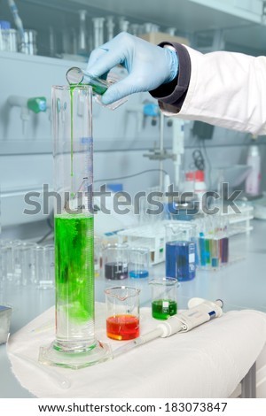 A Doctor is filling a large beaker with some alga liquid. - stock photo