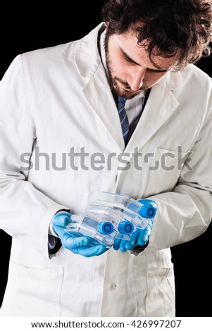 a doctor or researcher with a white lab coat holding a cell culture flask - stock photo