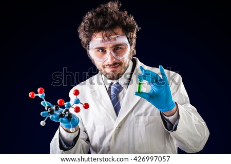 a doctor or researcher with a white lab coat holding a trinitrotoluene tnt molecular model and a vial with green fluid - stock photo