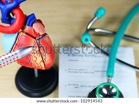 A doctor�s desk showing a green stethoscope, on a sick certificate pad in the background, and in the foreground the doctors pen point to a model of the heart, indicating where the patients problem is. - stock photo