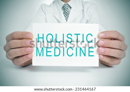 a doctor showing a signboard with the text holistic medicine written in it - stock photo