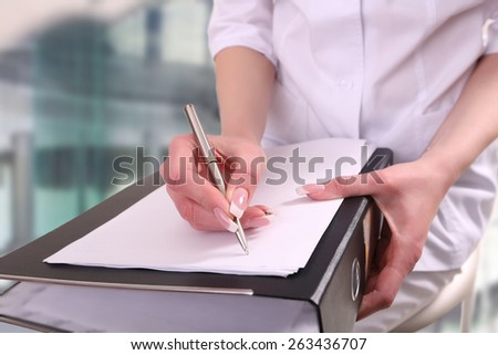 a doctor writing in a clipboard - stock photo