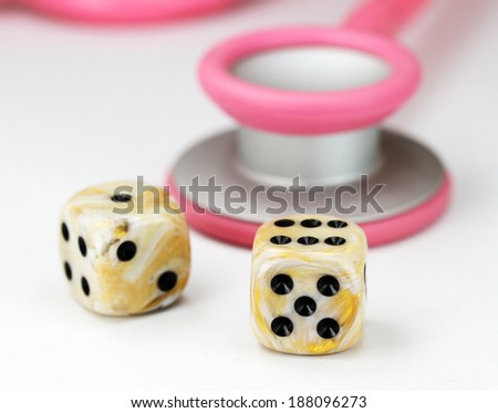 A Doctors Pink stethoscope with two white marbled dice with black spots dice placed next to it, asking the question, do you gamble with your health. - stock photo