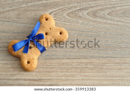 A dog biscuit with a blue bow  - stock photo