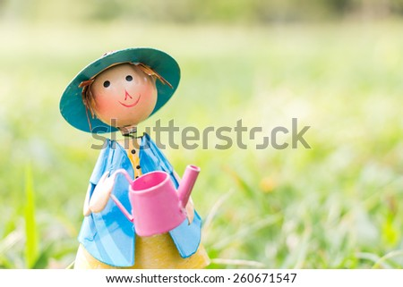 A doll standing holding water can on green grass background in a vintage retro style, with the sunrise, for the day of comfortable - stock photo