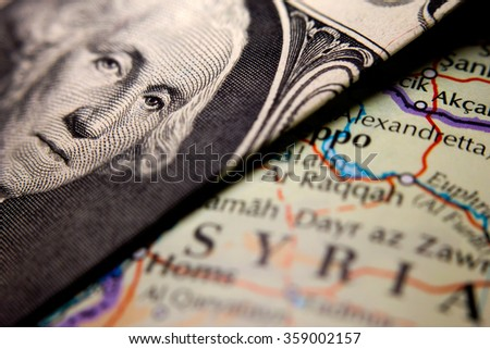 A dollar bill (figuring George Washington) on top of a map of Syria - stock photo