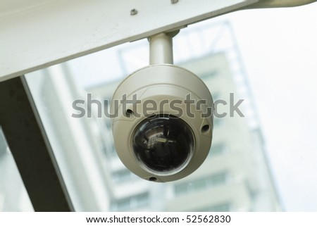 A dome-type security camera mounted on a ceiling - stock photo