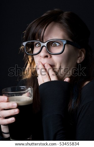 A dorky girl with goofy glasses on black background drinking a beer and making a face like it's not very good. - stock photo