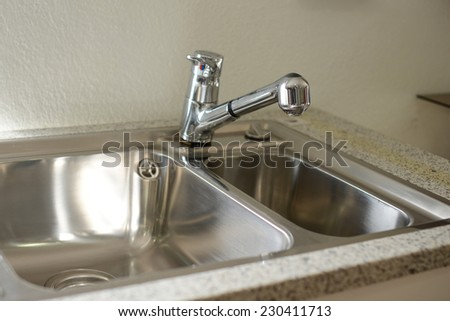 A double bowl stainless steel kitchen sink on a white granite worktop  - stock photo