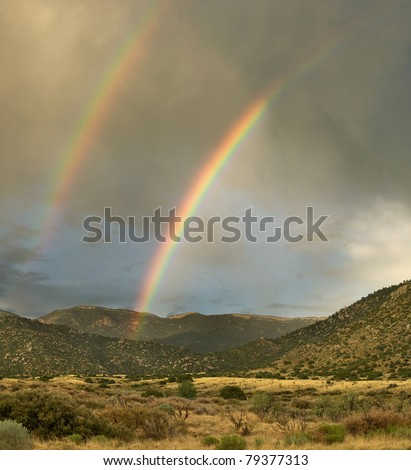 A double rainbow appears over Albuquerque's Sandia Mountains during the monsoon season - stock photo