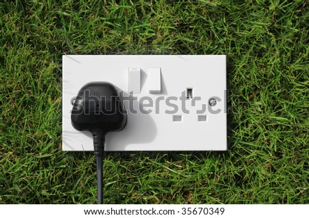 A double three pinned electrical socket with a black plug set in one unit. Set on green grass representing green energy/power. - stock photo