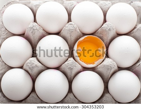 A dozen of eggs in  carton, one broken and exposing the yolk - stock photo