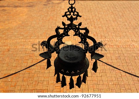 A dragon decoration plate hanging above a brick ground - stock photo