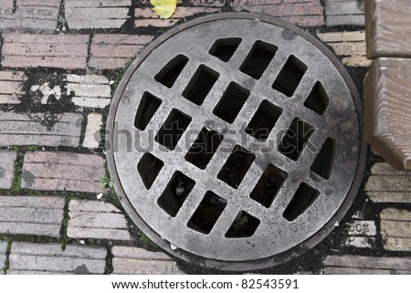 A drain cover in a pathway of aged bricks. - stock photo