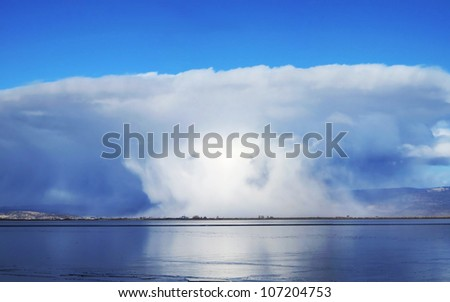 A dramatic cloudburst over a small town in the Klamath region of California. It was sunny and blue skies where the photo was shot from across the frozen lake - stock photo