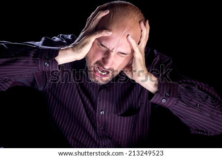 a dramatic image of a man yelling. He is very stressed out and the dramatic lighting helps emphasize it. - stock photo