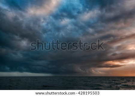 A dramatic rain formation in the distant Pacific Ocean pours rain in a small section of cloud cover - stock photo