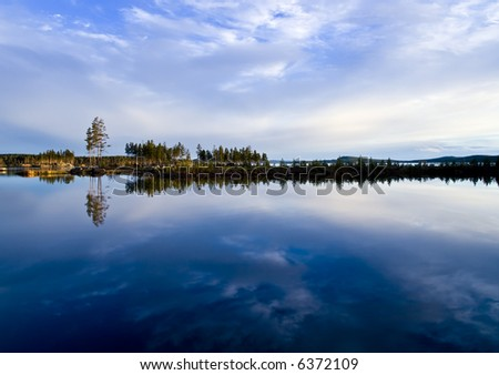 A dramatic sky reflecting in a calm northern lake - stock photo