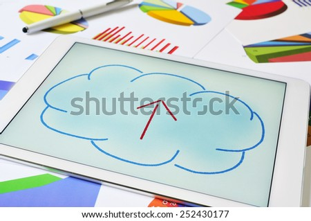 a drawing of a cloud with an arrow inside on the screen of a tablet, depicting the concept of upload to the cloud storage - stock photo