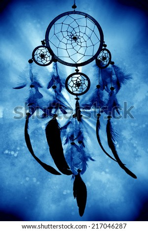 a dreamcatcher on a blue mystical background - stock photo