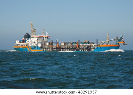a dredger sailing at sea - stock photo