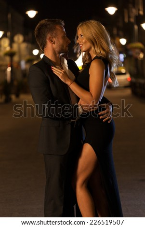 A dressed up couple embracing in a city at night - stock photo
