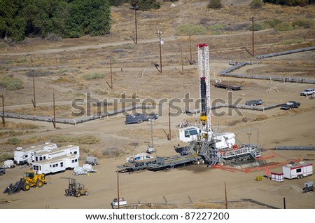 A drilling rig sets up on an existing oil lease - stock photo