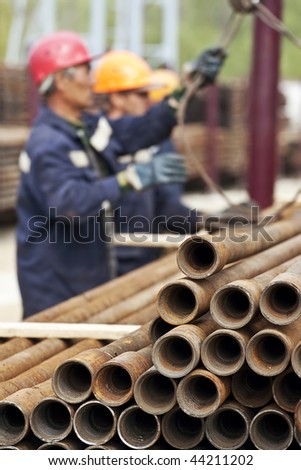 A drilling rig workers. Focus is on the pipes. - stock photo