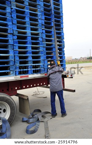 A driver unloads his cargo of wooden pallets delivered to a winery - stock photo