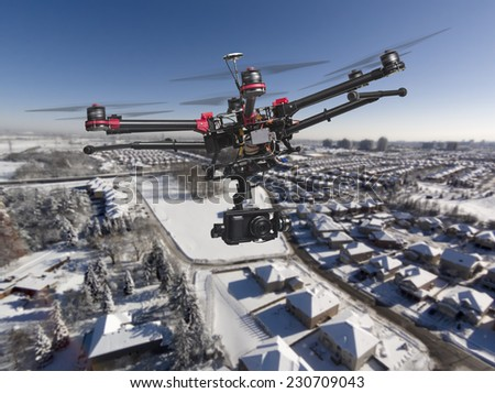 A drone with a camera and raised landing gears flying high above a residential area covered with fresh snow in a bright sunny winter day. - stock photo