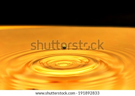 a drop of water falls in a golden water. macro - stock photo