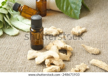 A dropper bottle of ginger root essential oil. Dried ginger root in the background on sackcloth. Free space for a text  - stock photo