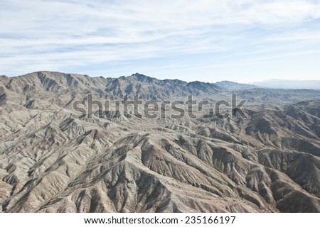 A dry desert view on a sunny day from a helicopter. - stock photo