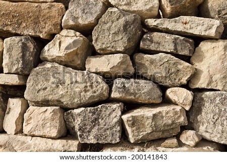 A dry stone wall made of random grey stone.  - stock photo