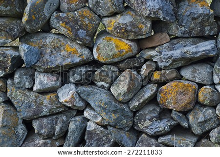 A dry stone wall made of random grey stone with grass at bottom. - stock photo
