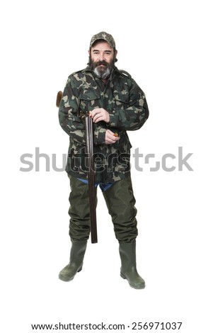 A duck hunter in waders and camo loading a double barreled shotgun on a white background. - stock photo
