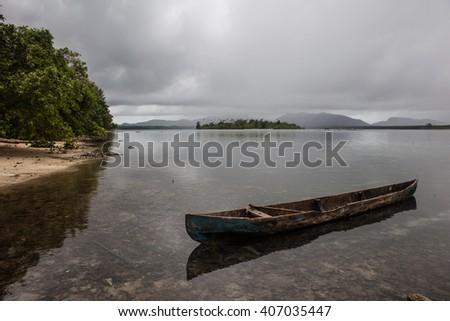 A dugout canoe, made from one large tree, floats in the shallows near a village in the Solomon Islands. Canoes continue to be one of the main means of transportation between islands in this region. - stock photo