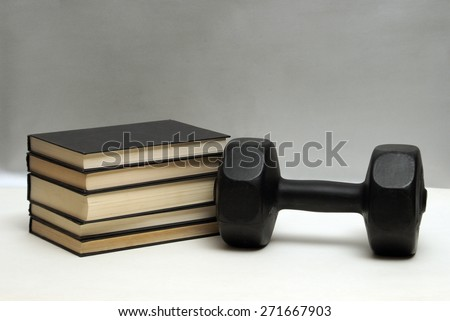 A dumbbell and stack of books for the concept of learning to be fit and healthy. - stock photo